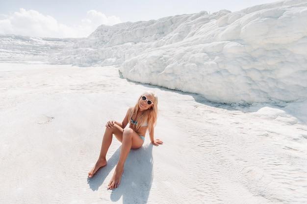 白い山、晴れた夏の日、パムッカレ、トルコの水着とサングラスの少女。