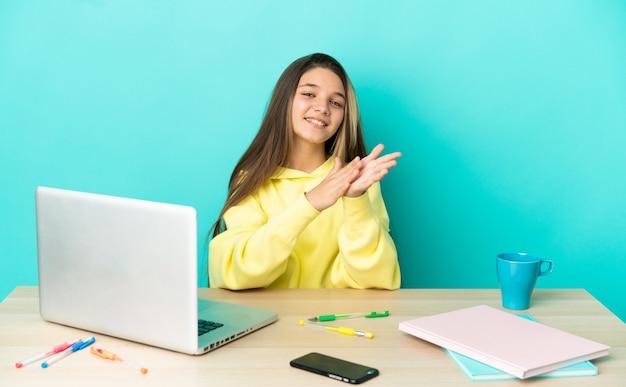 Маленькая девочка за столом с ноутбуком на изолированном синем фоне аплодирует после презентации на конференции