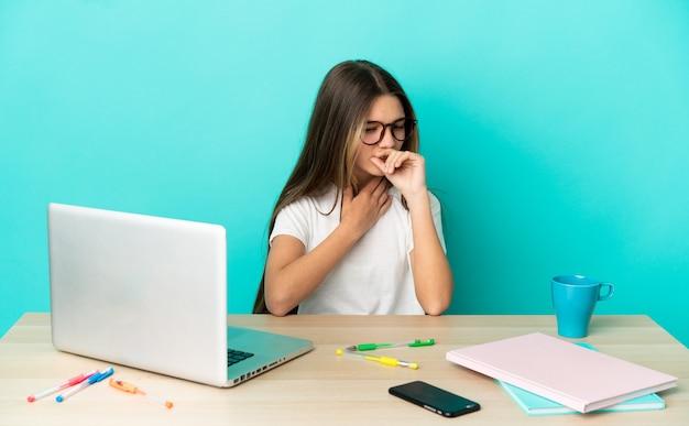Маленькая девочка за столом с ноутбуком на изолированном синем фоне много кашляет