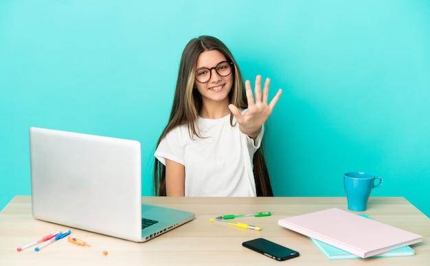 Маленькая девочка в столе с ноутбуком на изолированном синем фоне, считая пять пальцами