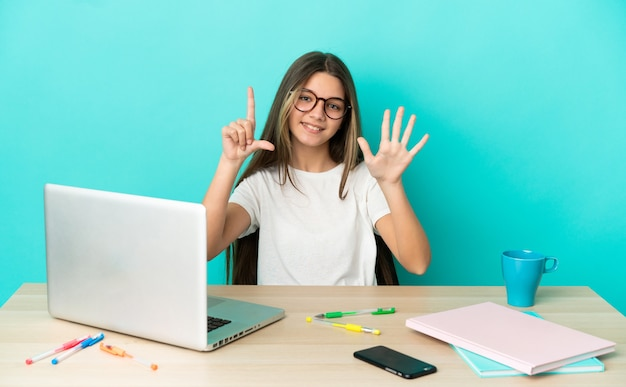 Маленькая девочка в столе с ноутбуком на изолированном синем фоне, считая семь пальцами