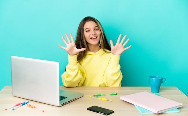 Маленькая девочка в столе с ноутбуком на изолированном синем фоне, считая десять пальцами