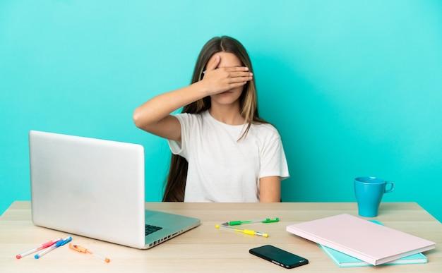 Маленькая девочка в таблице с ноутбуком на изолированном синем фоне, закрывая глаза руками. не хочу что-то видеть
