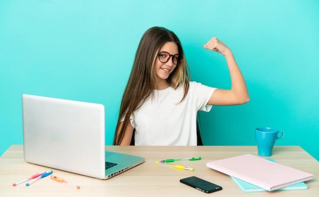 Маленькая девочка в столе с ноутбуком на изолированном синем фоне делает сильный жест