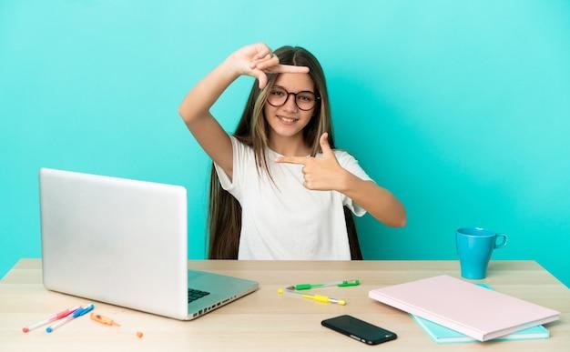 Маленькая девочка в таблице с ноутбуком на изолированном синем фоне, фокусируя лицо. обрамление символа