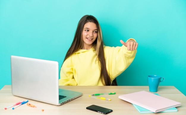 Маленькая девочка в столе с ноутбуком на изолированном синем фоне, показывая большой палец вверх жест