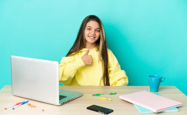 Маленькая девочка в столе с ноутбуком на изолированном синем фоне, показывая большой палец вверх