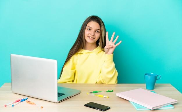 Маленькая девочка в столе с ноутбуком на изолированном синем фоне счастлива и считает четыре пальцами