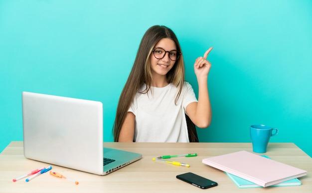 Маленькая девочка в столе с ноутбуком на изолированном синем фоне счастлива и указывая вверх