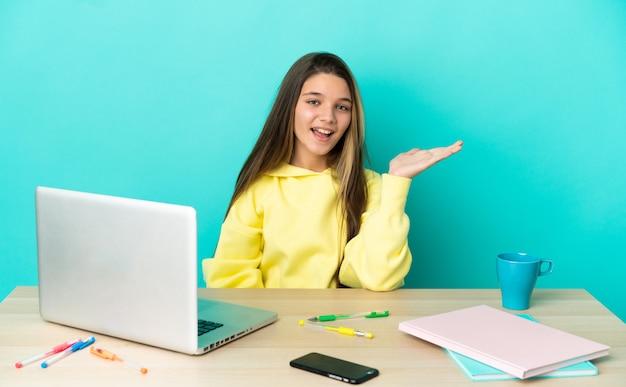 Маленькая девочка за столом с ноутбуком на изолированном синем фоне, держа на ладони воображаемое пространство, чтобы вставить рекламу