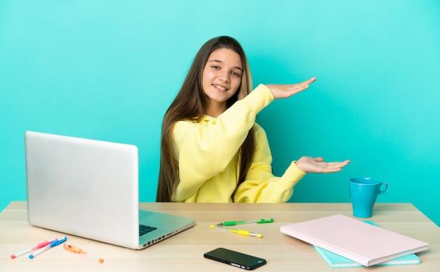 Маленькая девочка за столом с ноутбуком на изолированном синем фоне держит copyspace для вставки рекламы