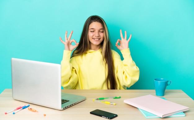 Маленькая девочка за столом с ноутбуком на изолированном синем фоне в позе дзен