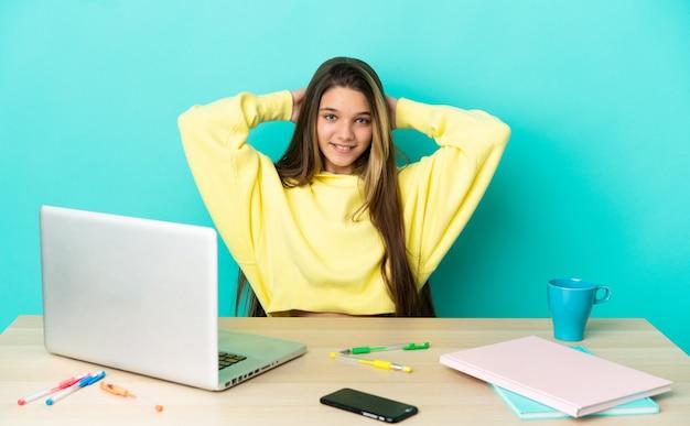 Маленькая девочка в столе с ноутбуком на изолированном синем фоне смеется