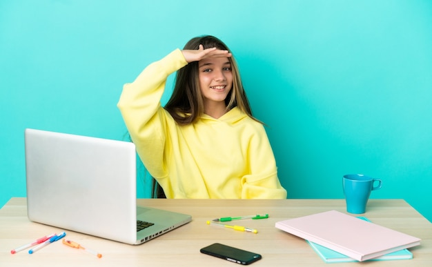 Маленькая девочка за столом с ноутбуком на изолированном синем фоне смотрит вдаль рукой, чтобы что-то посмотреть
