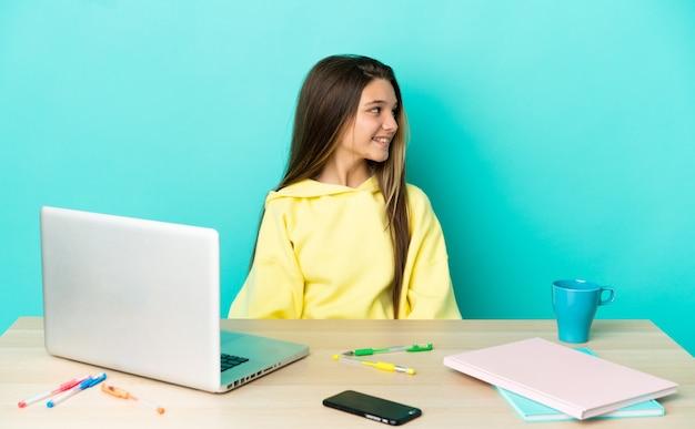 Маленькая девочка в столе с ноутбуком на изолированном синем фоне смотрит сторону