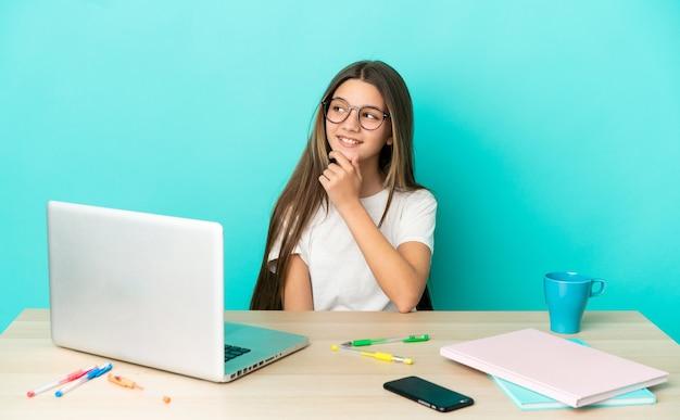 Маленькая девочка в столе с ноутбуком на изолированном синем фоне смотрит в сторону и улыбается