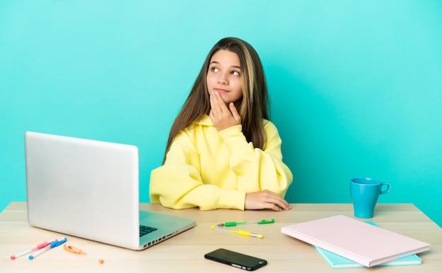 Маленькая девочка в столе с ноутбуком на изолированном синем фоне, глядя вверх, улыбаясь