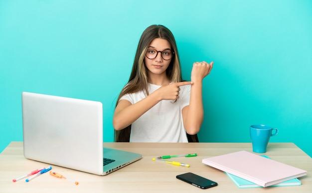Маленькая девочка за столом с ноутбуком на изолированном синем фоне делает жест опоздания