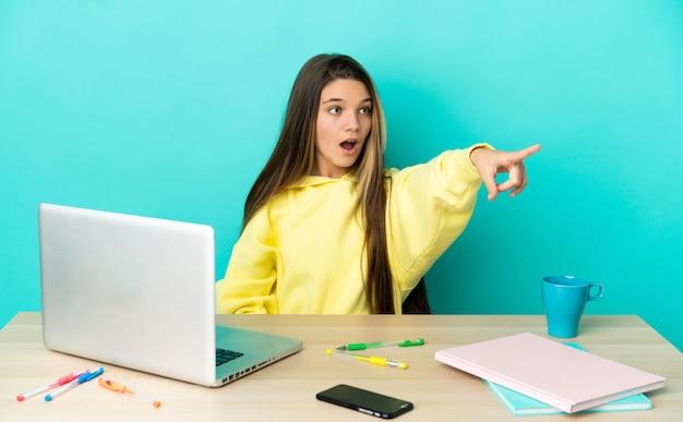 Маленькая девочка в столе с ноутбуком на изолированном синем фоне, указывая в сторону