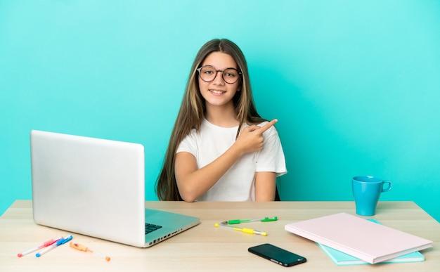 Маленькая девочка за столом с ноутбуком на изолированном синем фоне, указывая в сторону, чтобы представить продукт