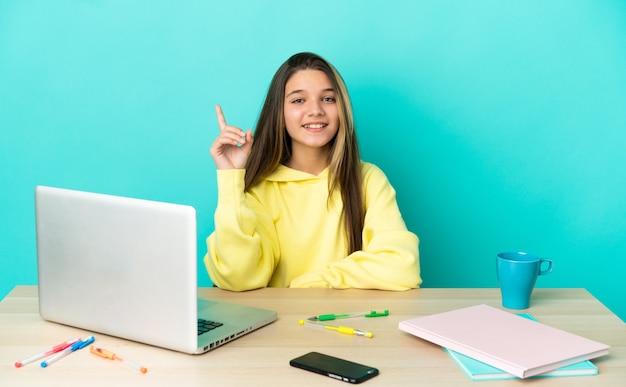 Маленькая девочка за столом с ноутбуком на изолированном синем фоне, указывая вверх отличную идею