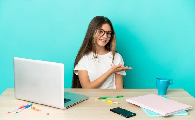 Маленькая девочка в столе с ноутбуком на изолированном синем фоне, представляя идею, улыбаясь в сторону