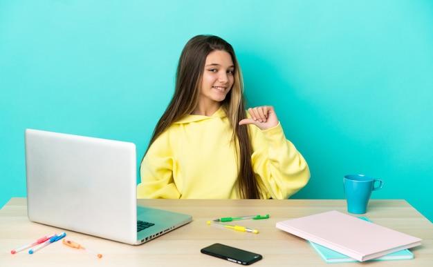 Маленькая девочка за столом с ноутбуком на изолированном синем фоне гордая и самодовольная