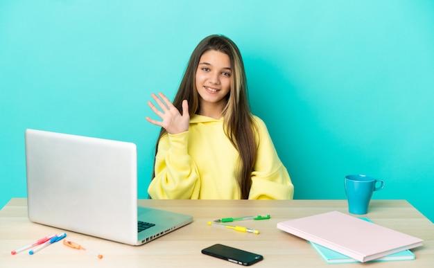 Маленькая девочка в столе с ноутбуком на изолированном синем фоне, салютуя рукой с счастливым выражением лица