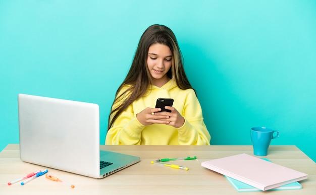 Маленькая девочка за столом с ноутбуком на изолированном синем фоне, отправляя сообщение с мобильного телефона
