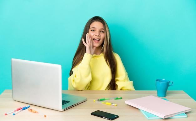 Маленькая девочка за столом с ноутбуком на изолированном синем фоне кричит с широко открытым ртом