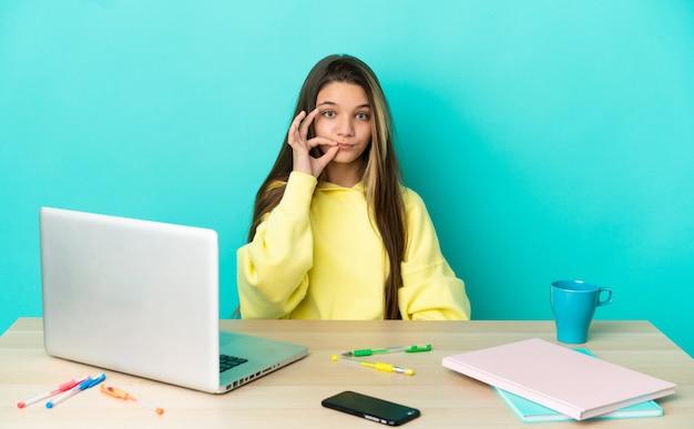 Маленькая девочка за столом с ноутбуком на изолированном синем фоне, показывая знак жеста молчания