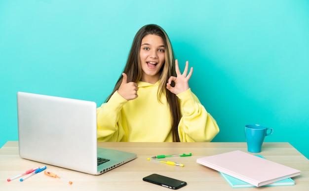 Маленькая девочка в столе с ноутбуком на изолированном синем фоне, показывая знак ок и жест пальца вверх