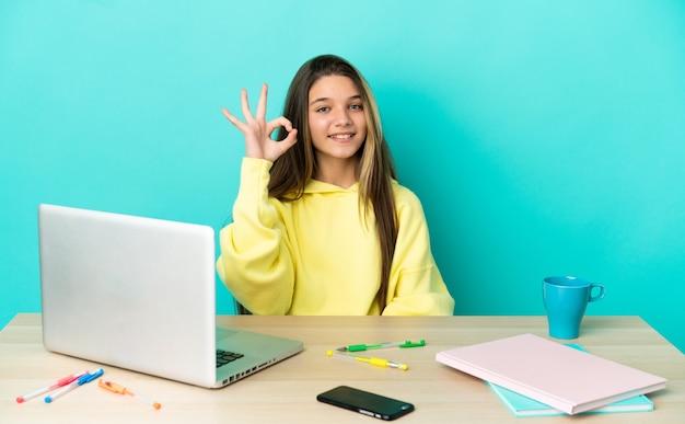 Маленькая девочка в столе с ноутбуком на изолированном синем фоне, показывая пальцами знак ок