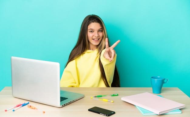 Маленькая девочка в столе с ноутбуком на изолированном синем фоне улыбается и показывает знак победы