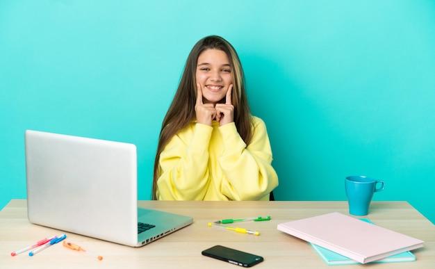Маленькая девочка за столом с ноутбуком на изолированном синем фоне улыбается со счастливым и приятным выражением лица