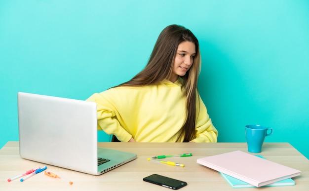 Маленькая девочка за столом с ноутбуком на изолированном синем фоне страдает от боли в спине из-за того, что приложила усилия