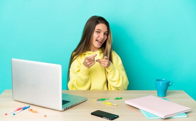 Маленькая девочка в столе с ноутбуком на изолированном синем фоне удивлена и указывает вперед