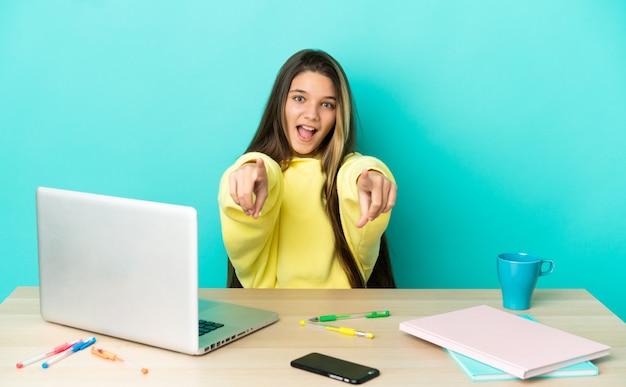 고립된 파란색 배경 위에 노트북이 있는 탁자에 있는 어린 소녀가 놀라 앞을 가리키고 있다