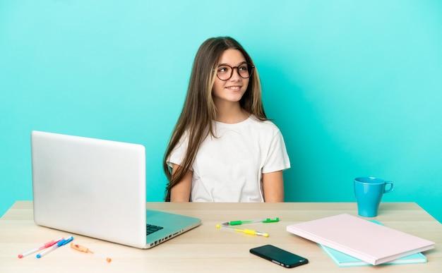 Маленькая девочка в столе с ноутбуком на изолированном синем фоне, думая об идее, глядя вверх