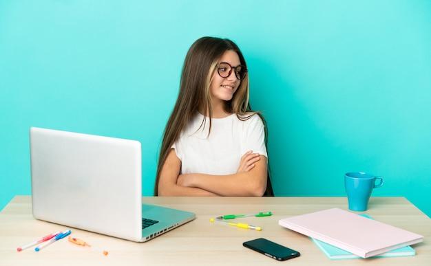 Маленькая девочка в столе с ноутбуком на изолированном синем фоне со скрещенными руками и счастливыми