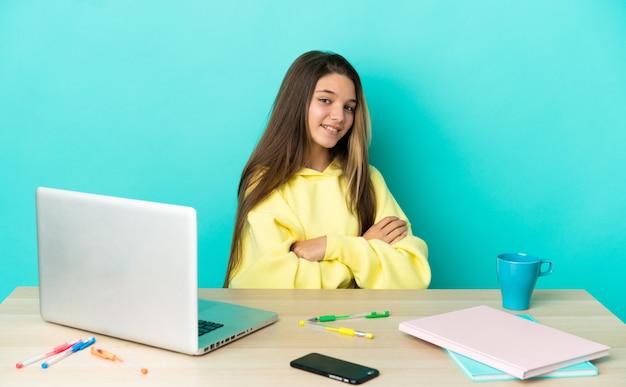 외진 파란색 배경 위에 노트북이 있는 탁자에 앉아 팔짱을 끼고 앞을 내다보는 어린 소녀