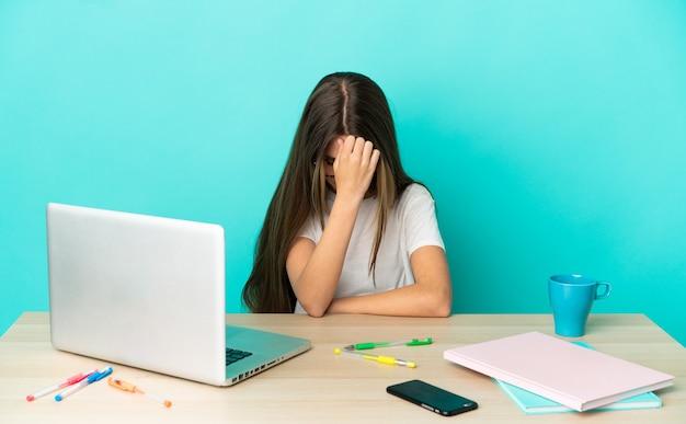 Маленькая девочка в столе с ноутбуком на изолированном синем фоне с головной болью