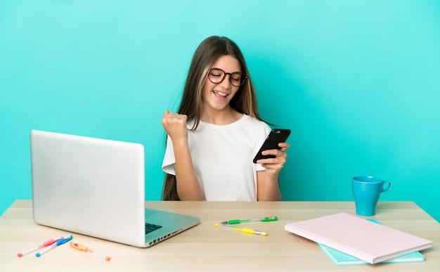 Маленькая девочка в столе с ноутбуком на изолированном синем фоне с телефоном в позиции победы