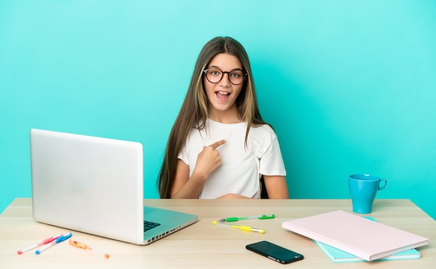 Маленькая девочка за столом с ноутбуком на изолированном синем фоне с удивленным выражением лица