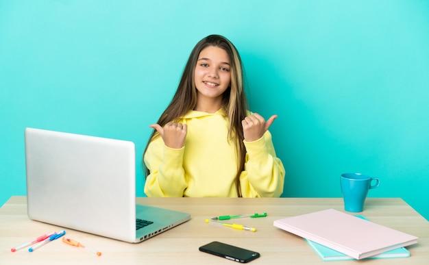 Маленькая девочка в столе с ноутбуком над изолированной синей стеной с большими пальцами руки вверх и улыбается