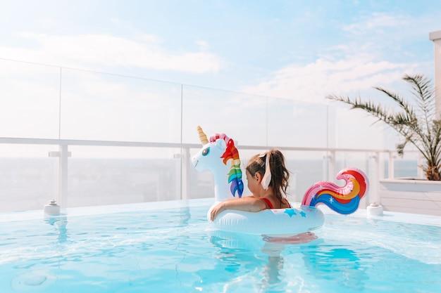 海を背景にシックなプールでユニコーンサークルの少女