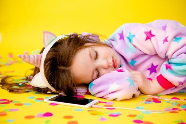 Маленькая девочка в кигуруми единорога наслаждается конфетти на желтом фоне