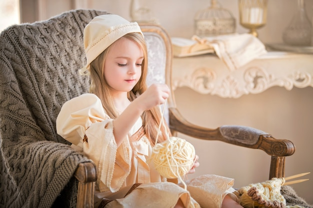 Маленькая девочка в винтажной ночной рубашке с клубком пряжи