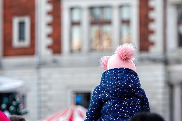 Маленькая девочка в теплой куртке и шляпе с кисточками на свежем воздухе в холодный день, вид сзади