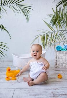 Маленькая девочка в белом банном полотенце сидит возле детской ванны и смотрит в камеру на белом фоне с местом для текста. водные процедуры для детей